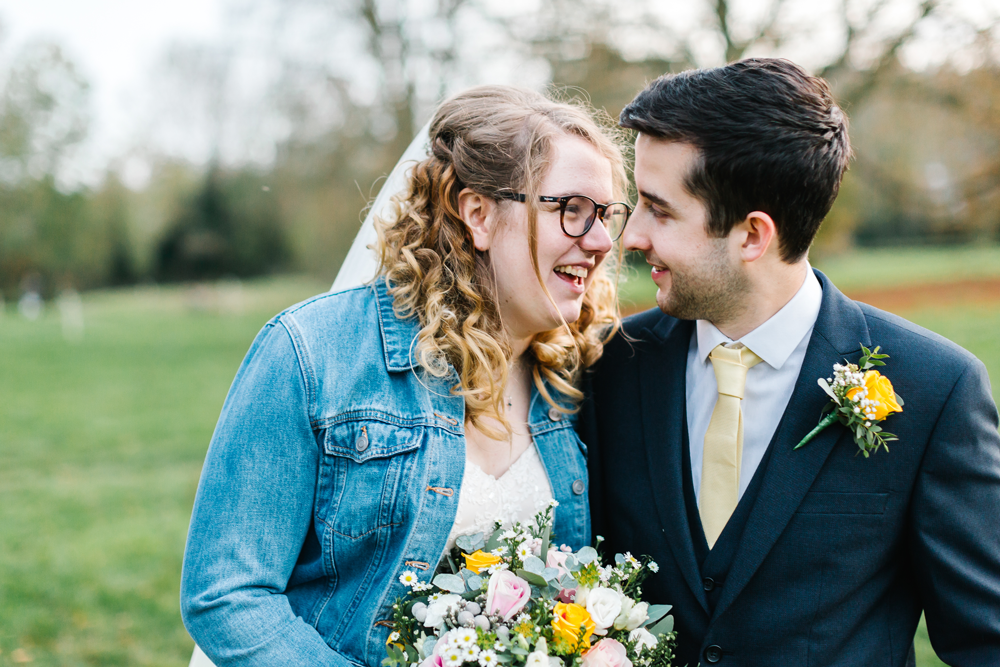 Brad and Grace on wedding day looking lovingly at each other, Grace is wearing her wedding denim jacket