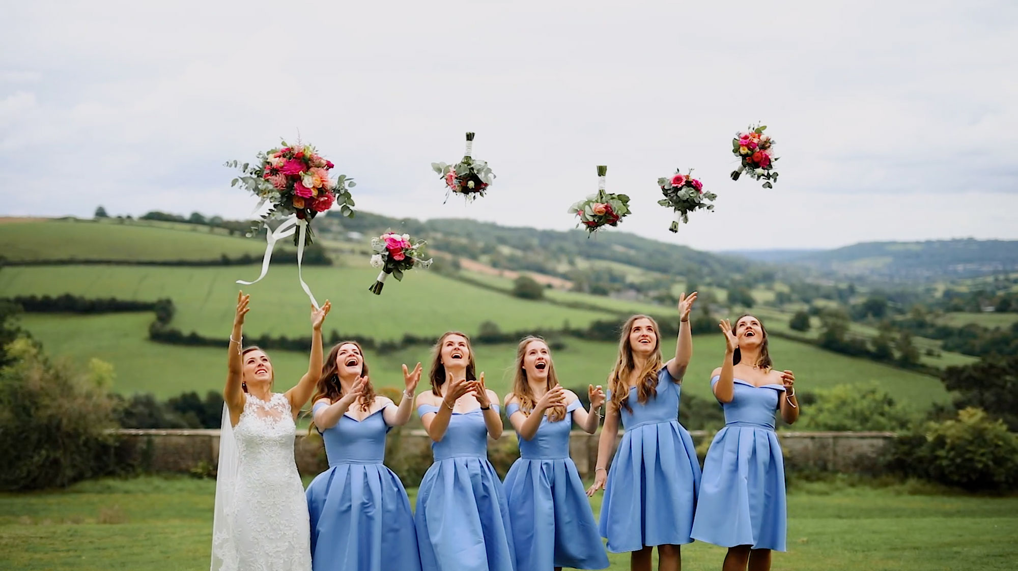 bride with bridesmaids throwing bouquets in the air with beautiful somerset views behind